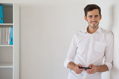 Casual businessman leaning against wall sending a text Stock Images