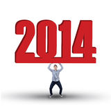 Casual businessman is lifting new year 2014 Royalty Free Stock Photography