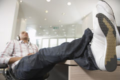 Casual Businessman Listening to Music With Feet On Desk Royalty Free Stock Photography