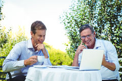 Casual businessman looking at laptop and having coffee Royalty Free Stock Images