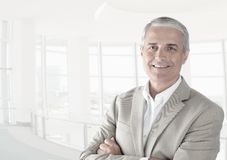 Casual businessman in a modern office with his arms folded royalty free stock images