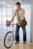 Casual businessman pushing his bike smiling at camera Royalty Free Stock Photography