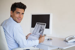 Casual businessman reading newspaper at his desk Royalty Free Stock Photos