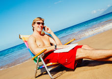 Casual Businessman Relaxing at the Beach with Laptop Computer Ta Royalty Free Stock Photos