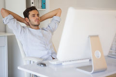 Casual businessman relaxing at desk leaning back Royalty Free Stock Photos