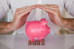 Casual businessman sheltering piggy bank and coins. In his office Royalty Free Stock Photo