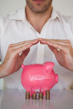 Casual businessman sheltering piggy bank and coins Stock Photography