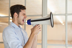 Casual businessman shouting through megaphone Stock Photography