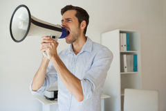 Casual businessman shouting through megaphone Royalty Free Stock Photography