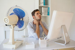 Casual businessman sitting at desk with electric fan Royalty Free Stock Images