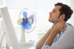 Casual businessman sitting at desk with electric fan Royalty Free Stock Photo