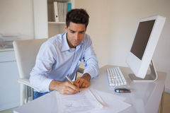 Casual businessman sitting at desk writing Royalty Free Stock Photos