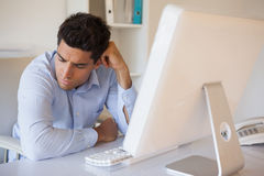 Casual businessman slumped at his desk Stock Images