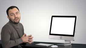 Casual businessman smiling and talking at the camera showing something on the monitor of computer on gradient background royalty free stock photo