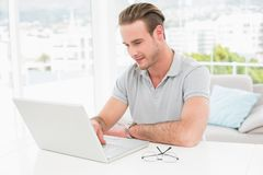 Casual businessman smiling and using laptop Royalty Free Stock Image