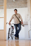 Casual businessman standing with his bike smiling at camera Royalty Free Stock Photography