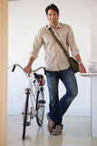 Casual businessman standing with his bike smiling at camera Stock Image