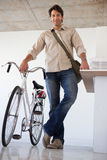 Casual businessman standing with his bike smiling at camera Royalty Free Stock Photos