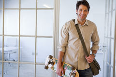 Casual businessman standing with his skateboard smiling at camera Stock Images