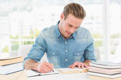 Casual businessman studying at his desk Royalty Free Stock Photos