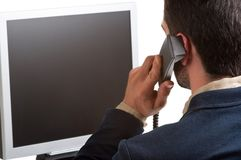 Casual Businessman Talking over the Phone and Looking at a Compu Stock Photography