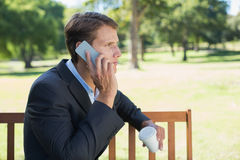 Casual businessman talking on phone on park bench with coffee Royalty Free Stock Photo