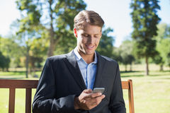 Casual businessman texting on phone on park bench Stock Photo