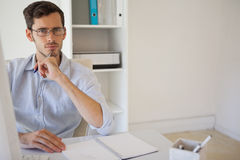 Casual businessman thinking at his desk Royalty Free Stock Image