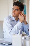 Casual businessman thinking at his desk Stock Images