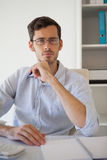 Casual businessman thinking at his desk Stock Photo
