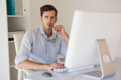 Casual businessman thinking at his desk Stock Image