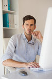 Casual businessman thinking at his desk Royalty Free Stock Photography