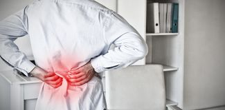 Composite image of casual businessman touching his sore back. Casual businessman touching his sore back against highlighted pain stock photos