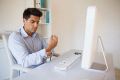 Casual businessman touching his sore wrist Stock Images