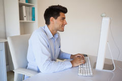 Casual businessman typing at his desk Stock Photography