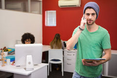Casual businessman using cellphone in office Royalty Free Stock Photo