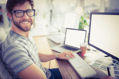 Casual businessman using computer in office. Portrait of a casual young businessman using computer in office Stock Photos