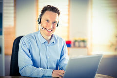 Casual businessman using headset on a call. In his office Stock Image