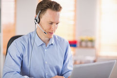 Casual businessman using headset on a call. In his office Royalty Free Stock Photos