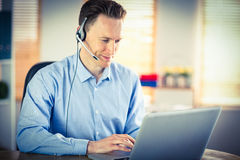 Casual businessman using headset on a call. In his office Stock Photos