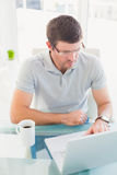 Casual businessman using his laptop at desk Royalty Free Stock Images