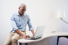 Casual businessman using his laptop at desk Stock Images