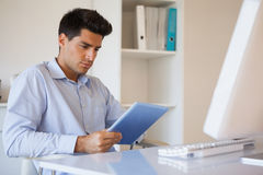 Casual businessman using his tablet at his desk Stock Image