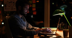 Casual businessman using laptop at night stock video footage