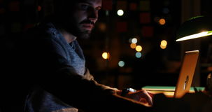 Casual businessman using laptop at night stock video