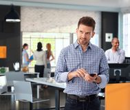 Casual businessman using mobile phone at office. Casual businessman using mobile phone at modern stylish office, smiling Stock Photo