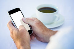 Casual businessman using smartphone and having coffee Royalty Free Stock Images