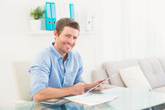 Casual businessman using tablet at desk Royalty Free Stock Image