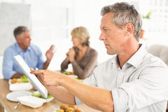 Casual businessman using tablet at lunch Royalty Free Stock Photography