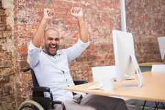 Casual businessman in wheelchair cheering at his desk Stock Photo